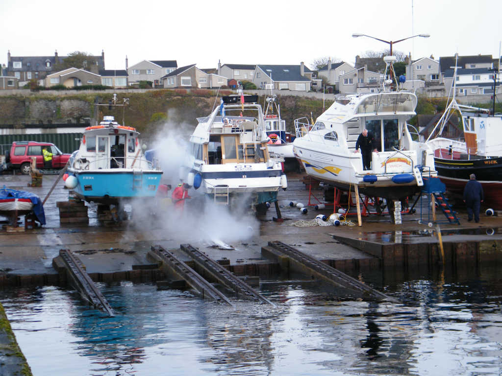 Photo: Lifting Small Boats Out Of The Water At Wick Harbour