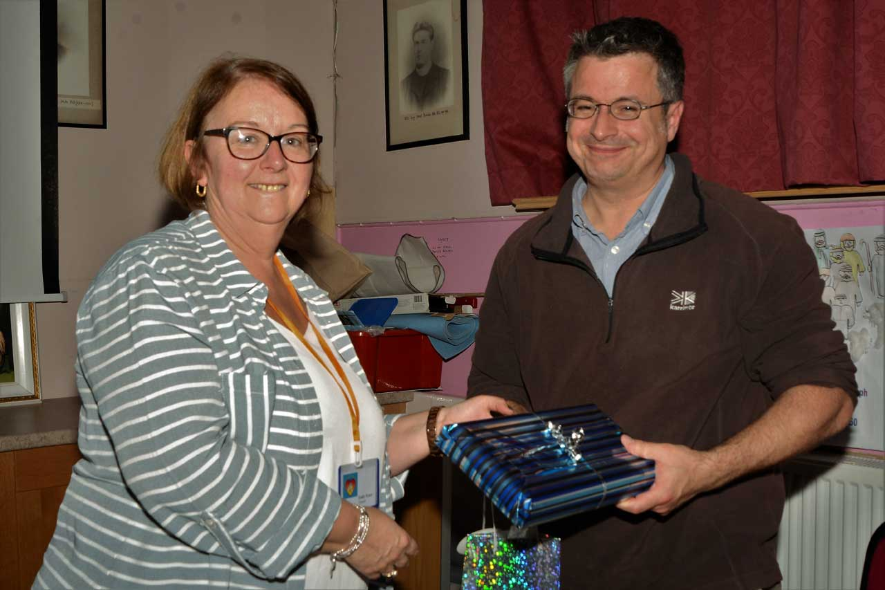 Photo: Dr Loughhead receives a gift from treasurer Emily Fraser
