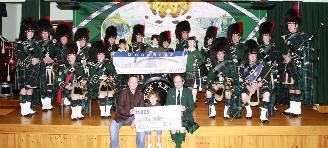 Photo: Wick Pipe Band Accepts £300 From UKAEA On Behalf of NDA