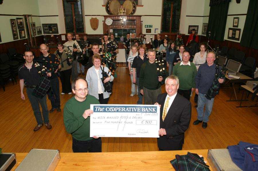 Photo: John Bogle, Secretary Of Wick Pipe Band Receives Scottish Co-op Cheque For £500