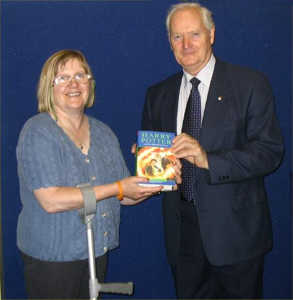 Photo: Mary Inkster Presents Raffle Winner Jimmy Johnston With Signed Harry Potter Book